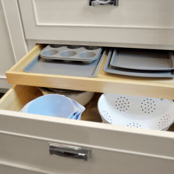Shallow Roll-Out Above Drawer used for Pan Storage. Kitchen cabinets and storage by Dura Supreme Cabinetry.
