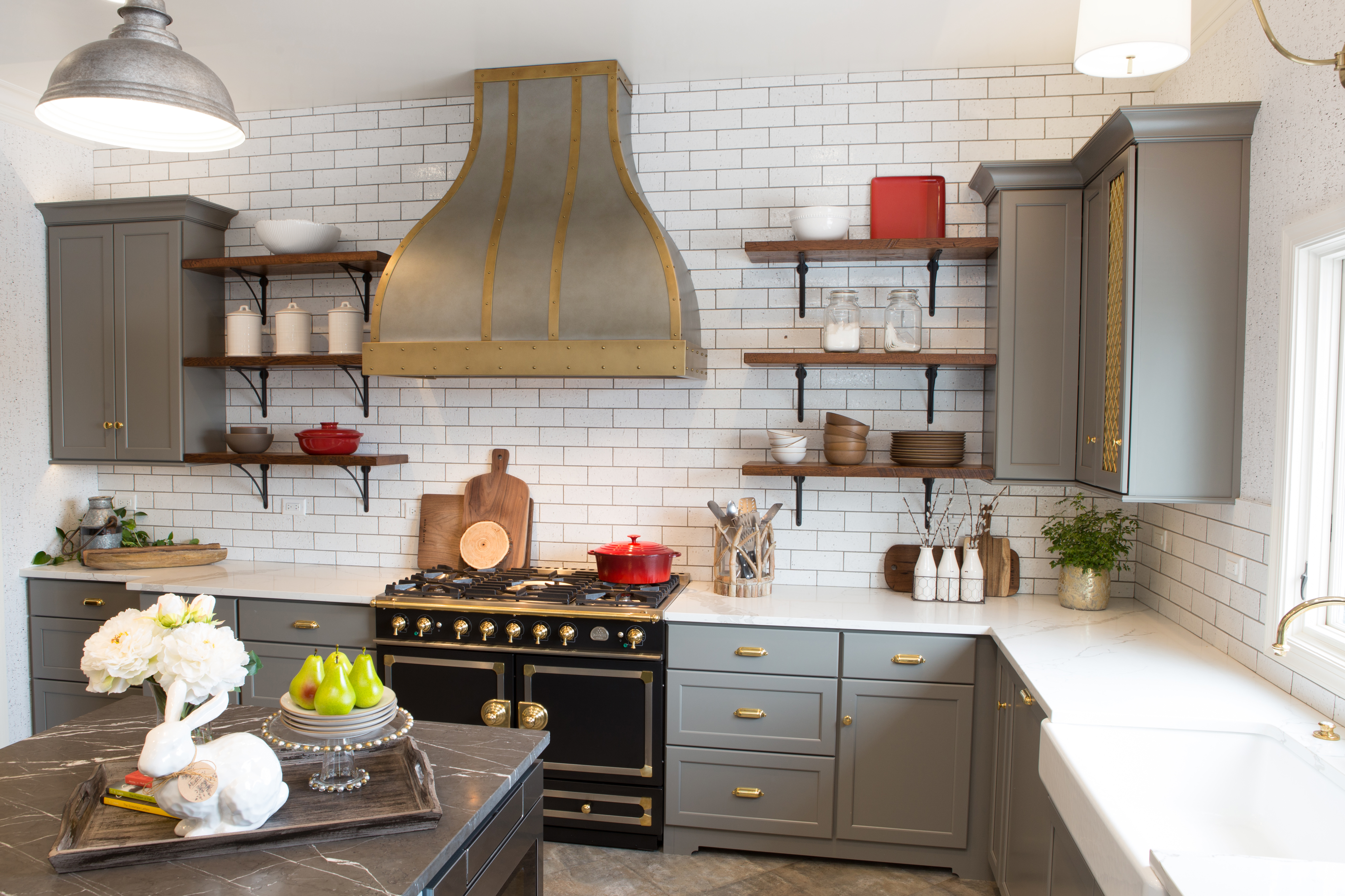Gray cabinets in a Gray, White, and Gold kitchen design. Beautiful custom Zinc and Brass range hood by Vogler Metalwork & Design proudly centers over the black enamel and brass LaCornue range.