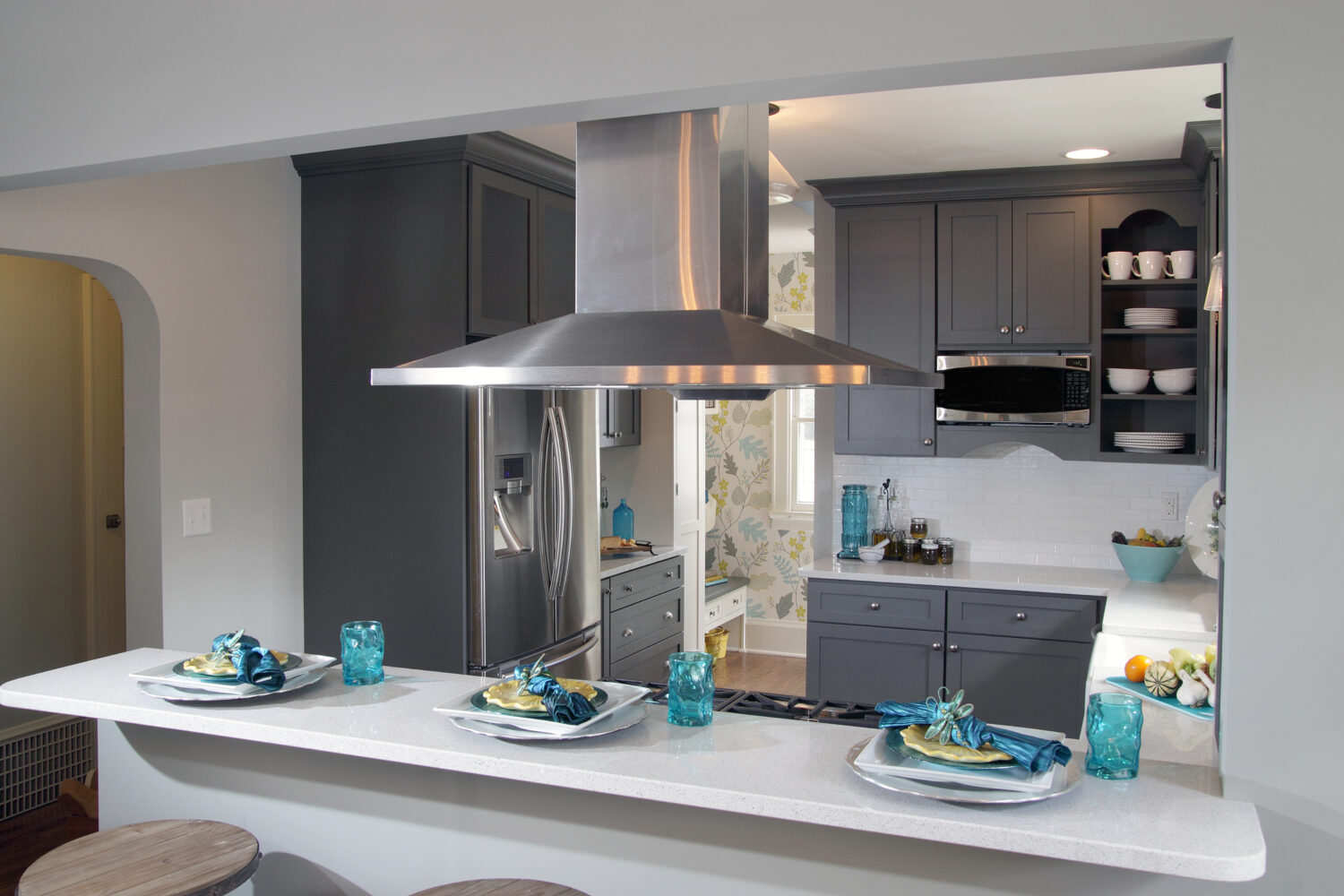 A dark gray painted kitchen deisgn with a peninsula with seating for guests to watch as the chef cooks and entertains.