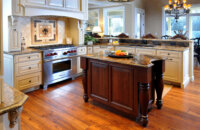 A stunning traditional styled kitchen design with a large wood hood and a table styled kitchen island.