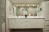 A fresh all-white, contemporary bathroom design by Dan Luck of Bella Domicile featuring Dura Supreme Cabinetry.