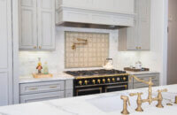 This elegant Dura Supreme kitchen adorned with brassy gold accents was designed by Joyce Van Den Dungen Bille of Gilmans Kitchens and Baths, California.