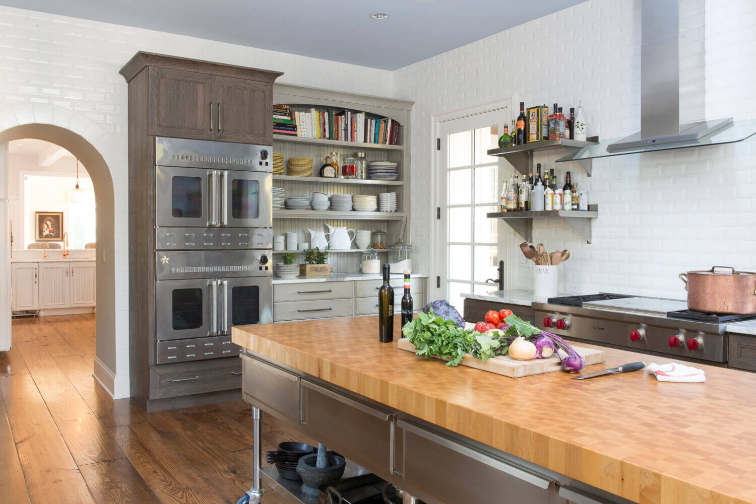 A long island with a butcher block countertop provides a large work service for food prep.