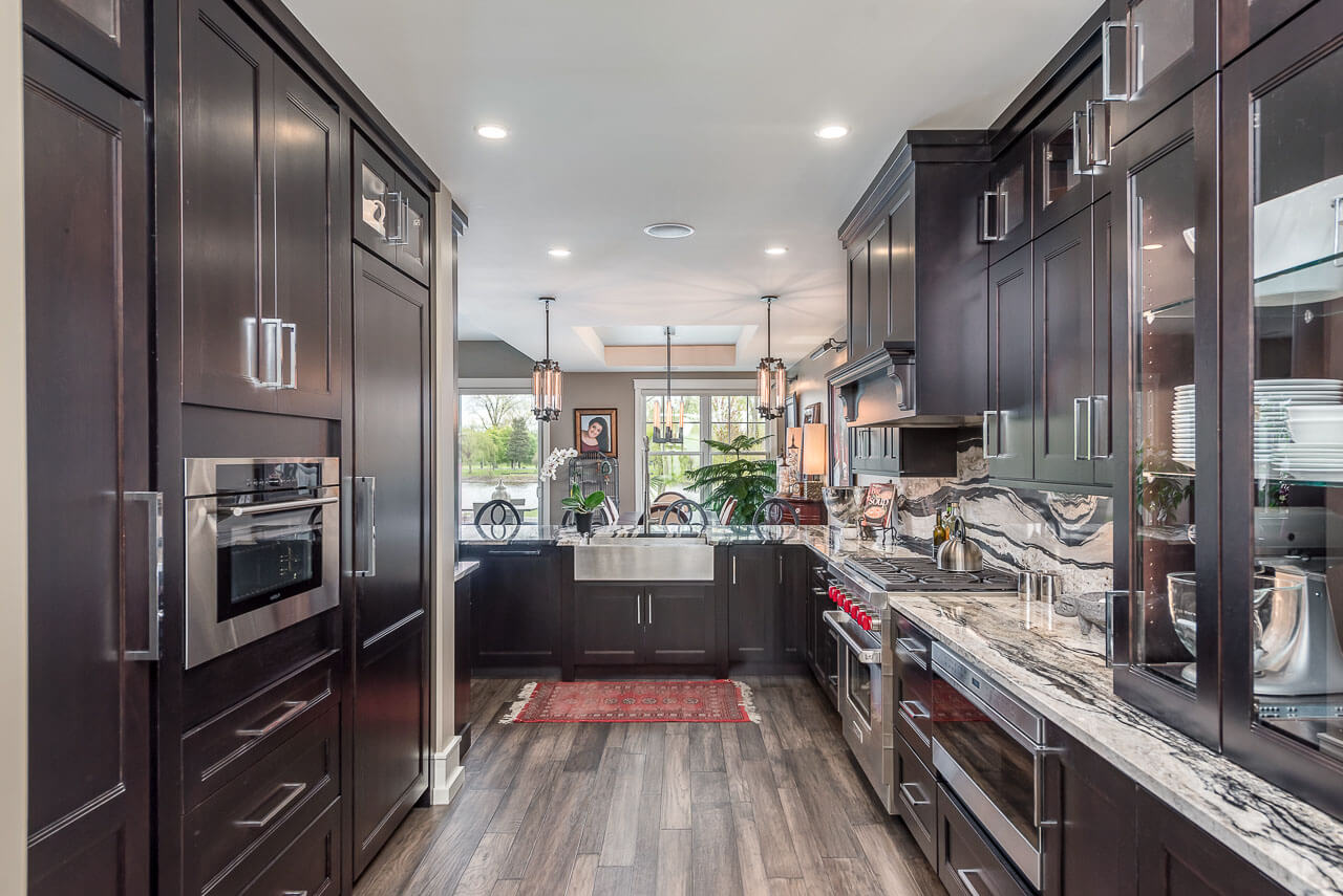 A dark kitchen with black stained cherry cabinets from Dura Supreme Cabinetry and beautiful black and white granite countertops.