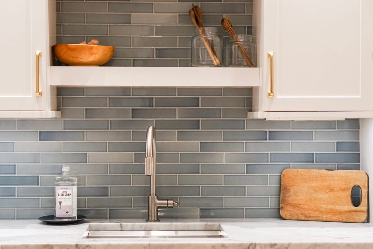 Close up of prep sink area with a floating and open shelf above, white cabinets, gold cabinet pulls, and a pale blue tiled backsplash.