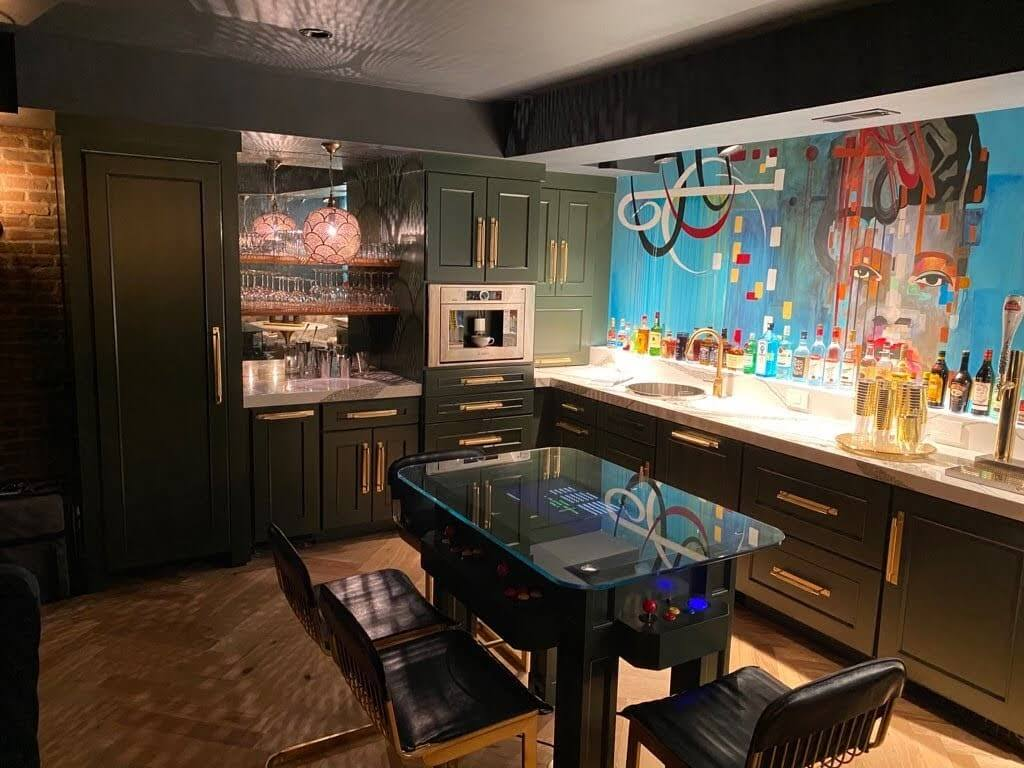 A home bar basement remodel with dark green cabinets and a mirror backsplash to bounce the decorative light patterns of the Moroccan pendant lights.