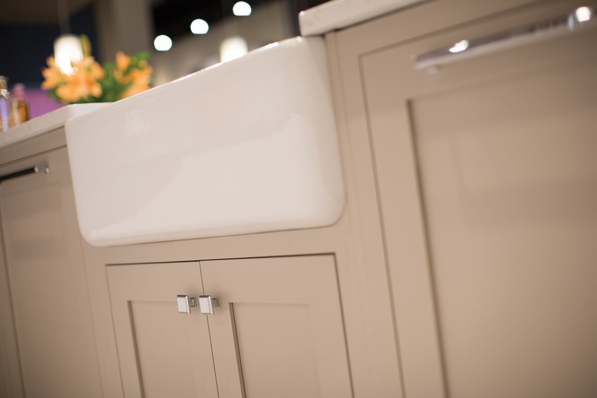 A close up of a beige or tan colored kitchen island from Dura Supreme Cabinetry with inset cabinet doors.