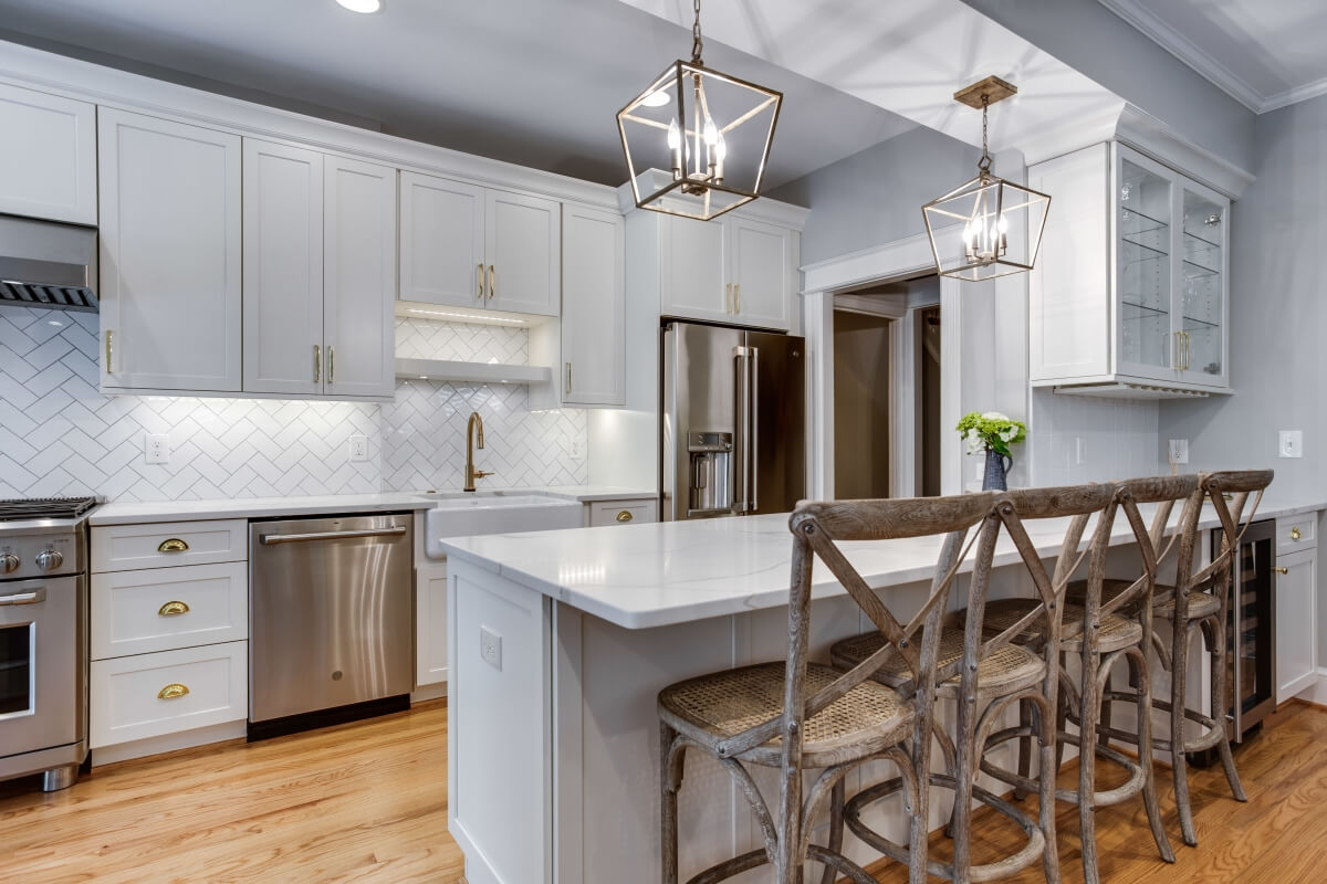 An all white kitchen with white painted cabinets, a long kitchen peninsula, a galley kitchen layout with white countertops and gold hardware.