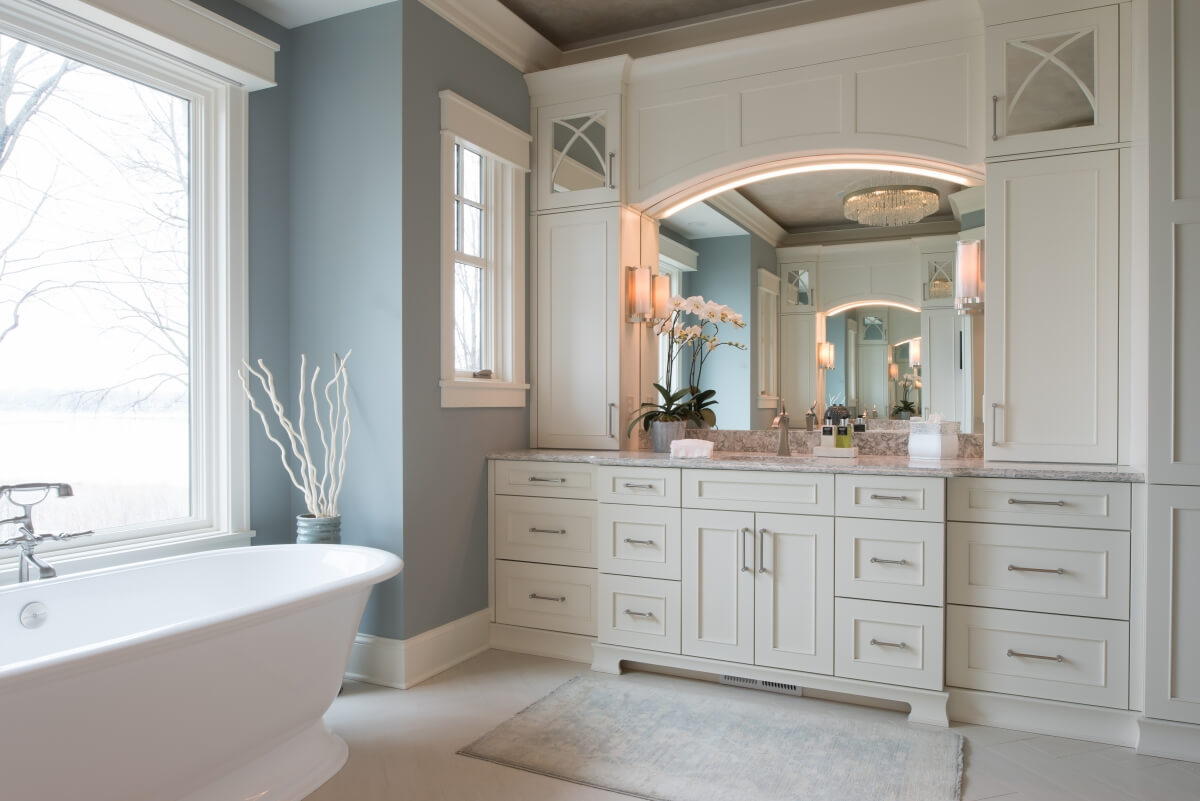 The upper cabinets use mirror to create the look of a glass accent door without the hassel of having to keep what's behind the cabinet neat and tidy. Dura Supreme master bathroom design by Michels Homes, Minnesota. Photography by Landmark Photography.