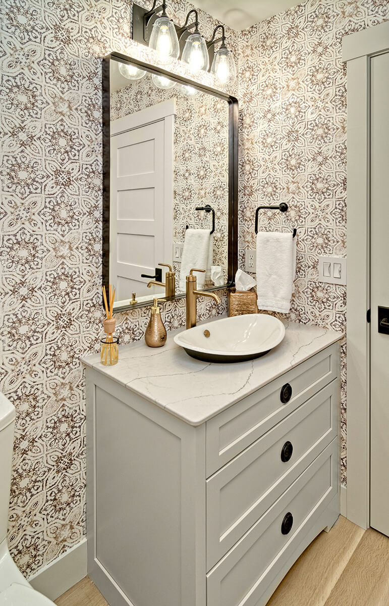 A trendy bathroom design with wallpaper design, shinny brass hardware, black light fixtures and a warm gray painted bathroom vanity.