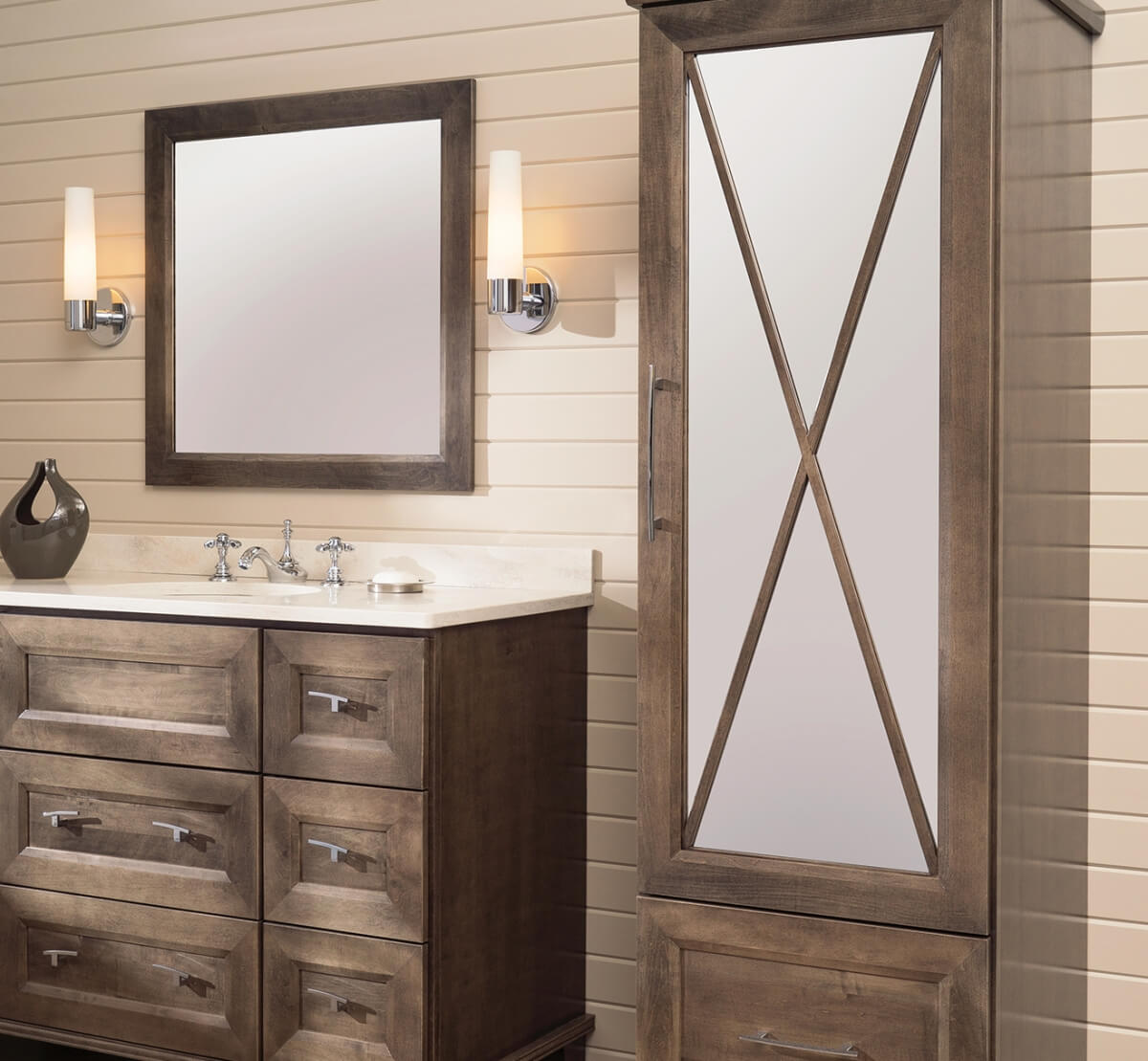 Light to Medium stained bathroom vanity and linen cabinet with an X pattern mullion door with a tall mirror glass insert in the cabinet door.