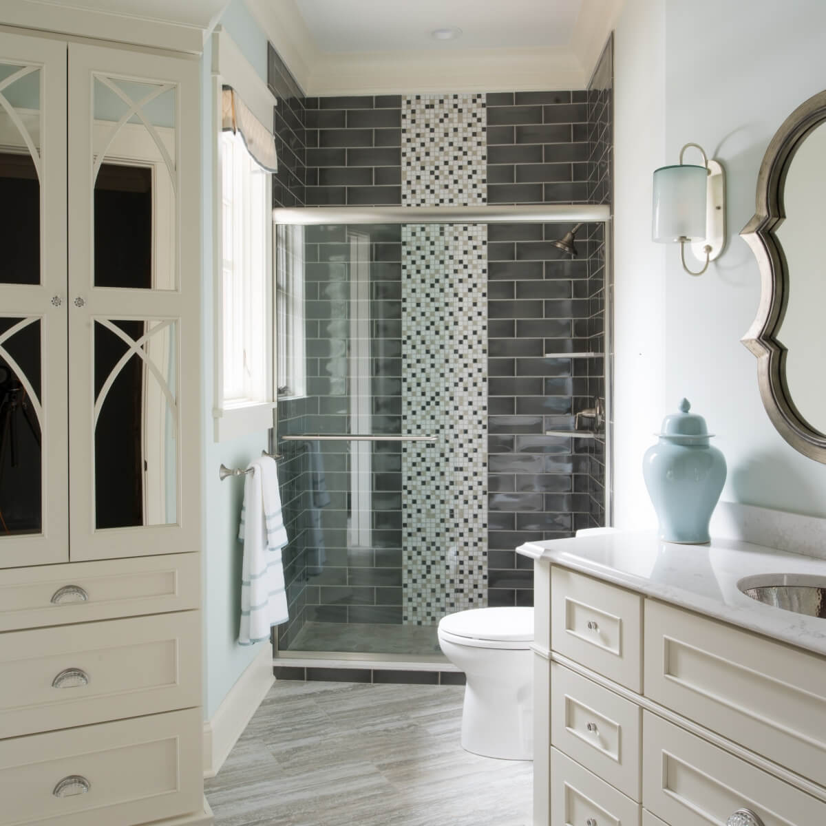 A stunning all white master bathroom with beautiful mullion cabinet doors with mirror glass inserts.