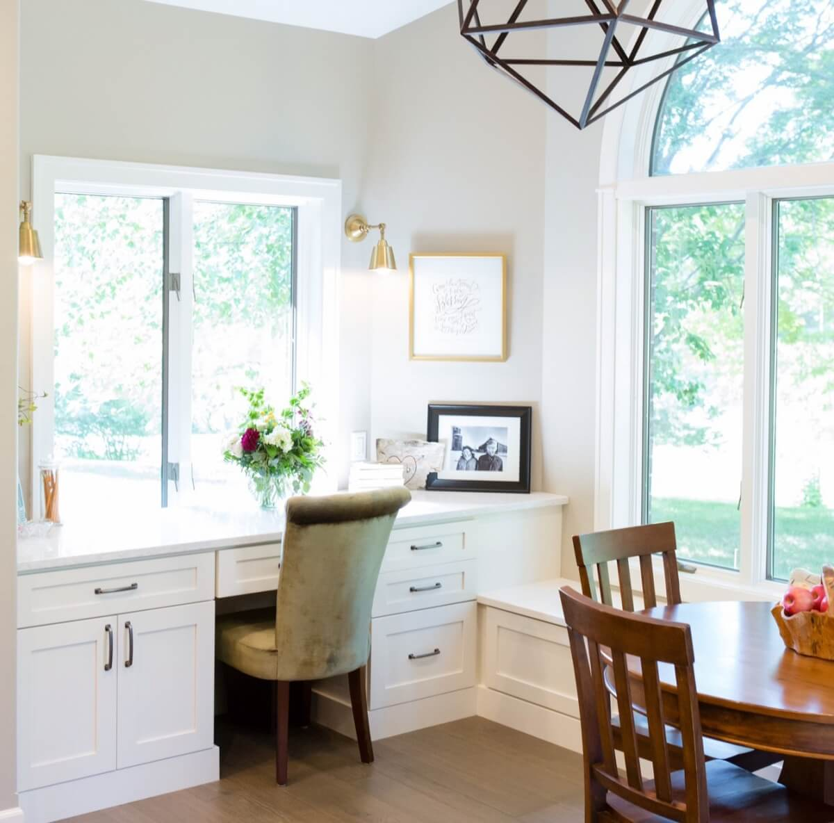 A stunning home office in the diining room with white cabinets and home office desk.