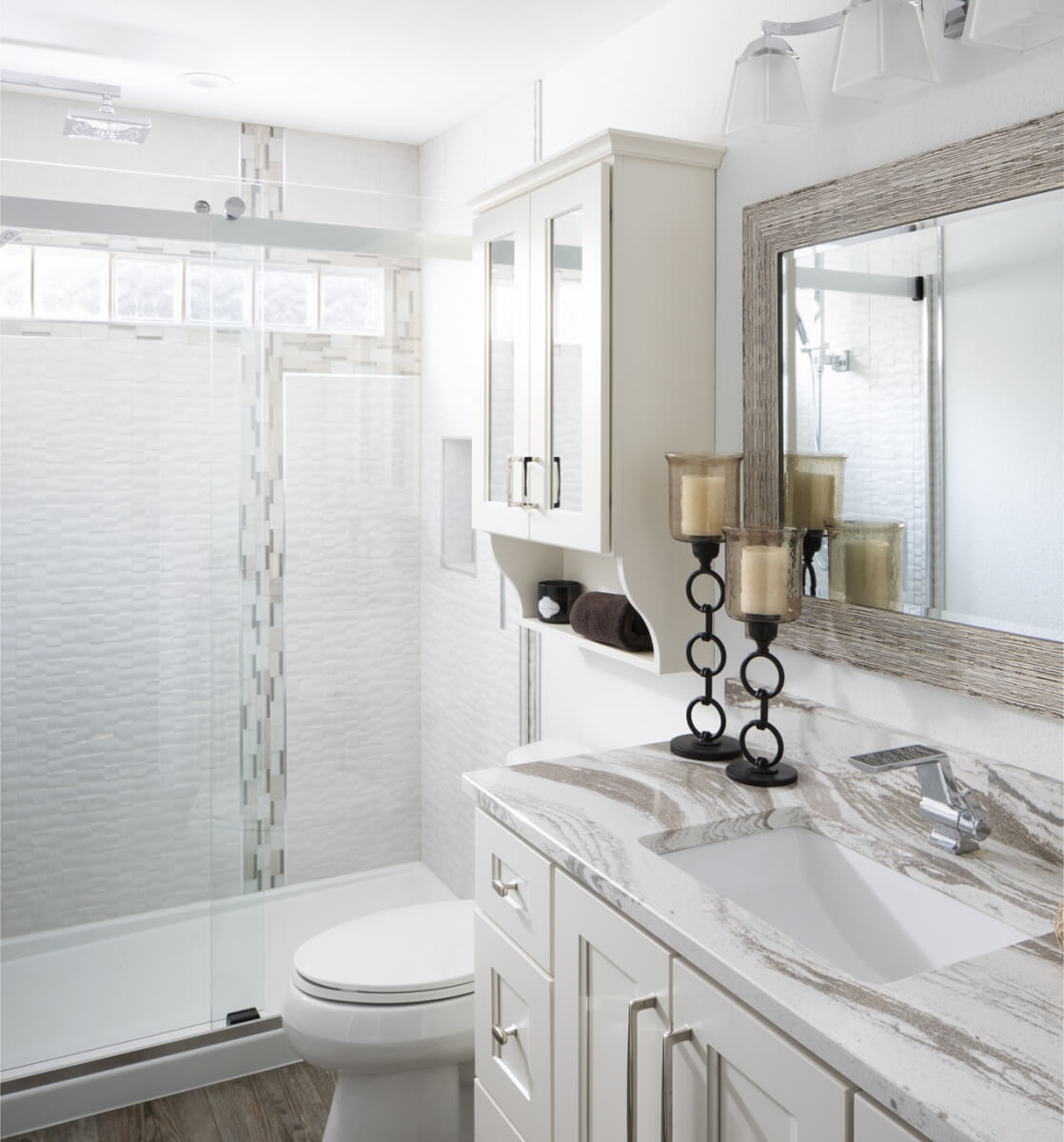 The small cabinet above the toilet in this bathroom uses mirror to help reflect more light from the small bathroom window throughout the space. Dura Supreme design by Gwen Adair of Cabinet Supreme by Adair, Wisconsin. Photography by Ryan Hainey.