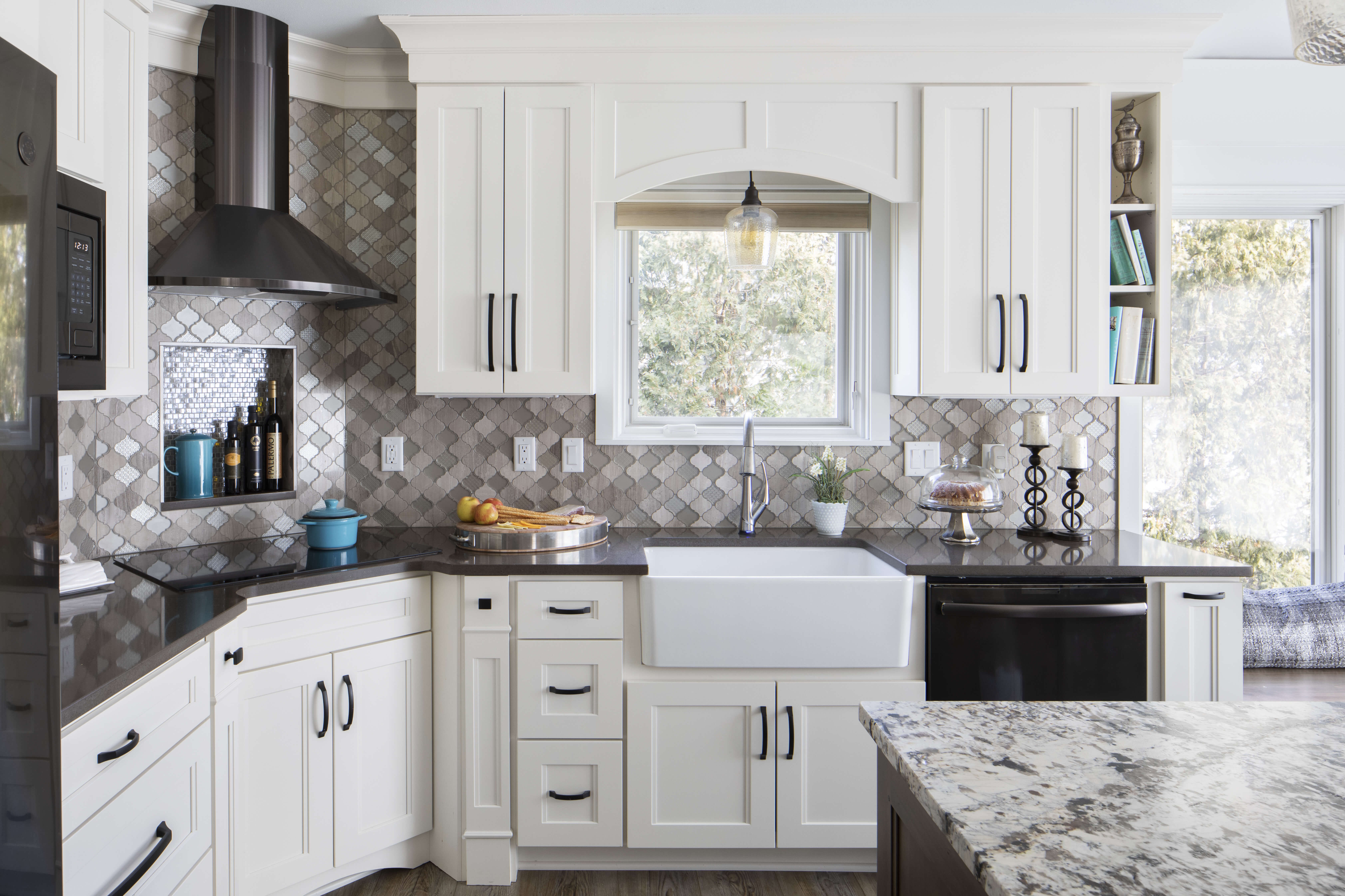 A transitional kitchen with white painted cabinets, black stainless steel appliances and black countertops.