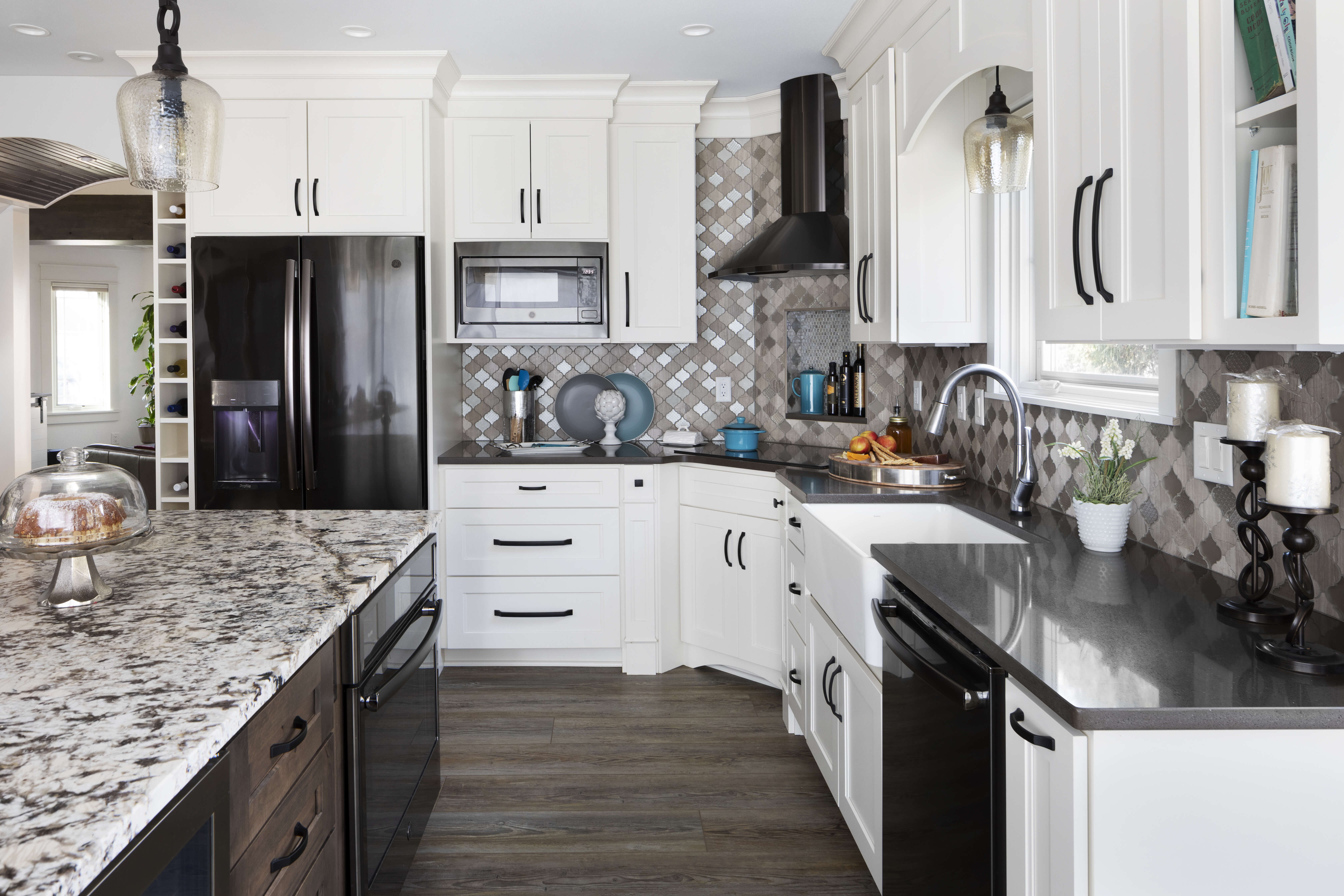 A kitchen remodel with a combination of white painted cabinets and a gray stained kitchen island featuring black countertops and black staineless steel appliances.