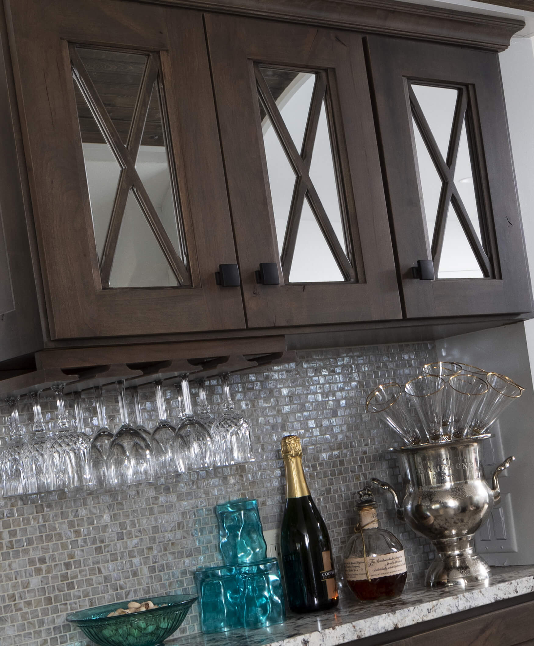 A close up of dark stained cabinets with mirror mullion cabinet doors.