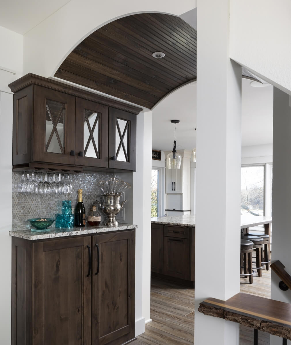 A beautiful hallway with a wet bar, mirrored cabinet inserts, and a barrel ceiling design.