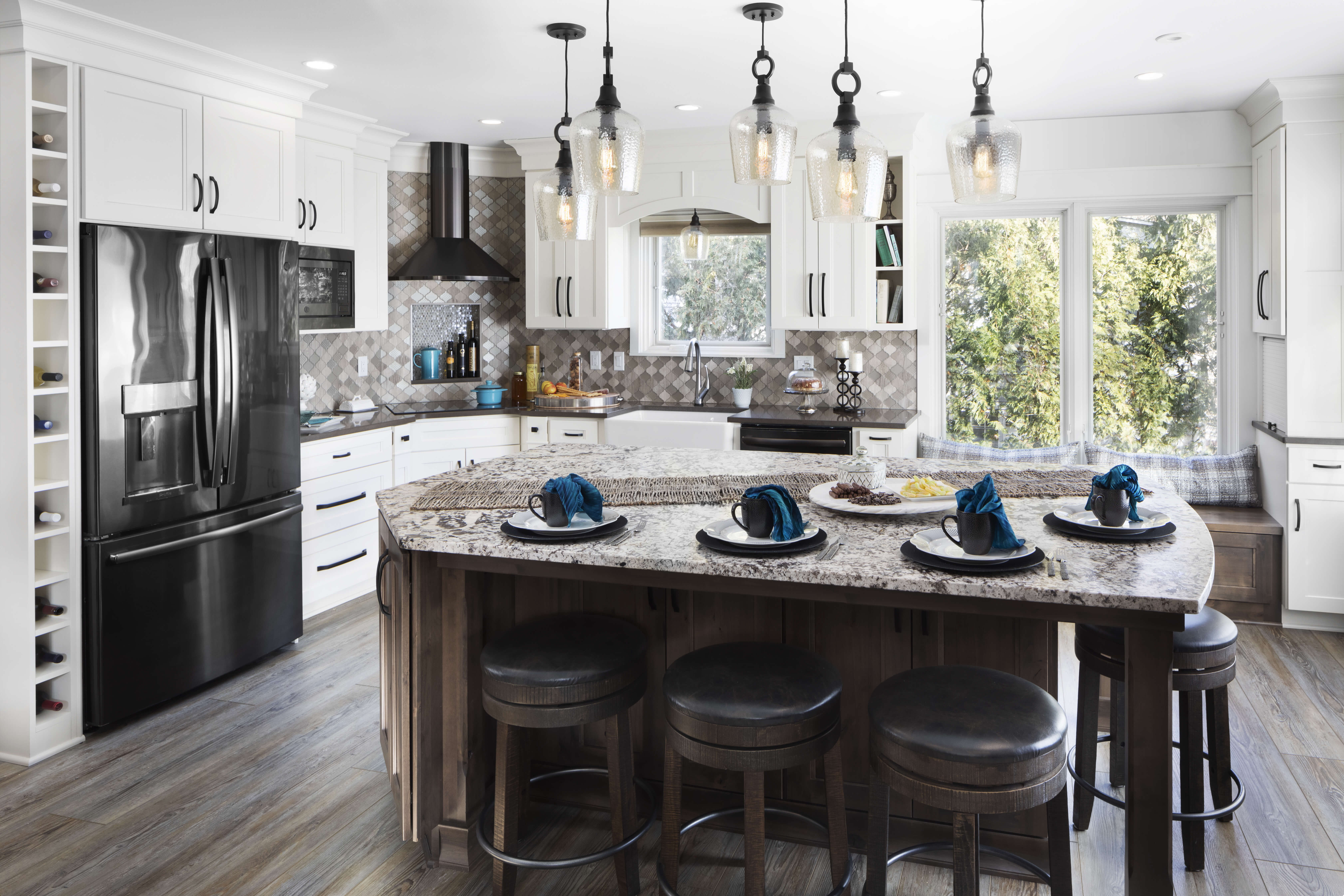 A beautiful lake house kitchen with a modern and casual style. The kitchen has white painted cabinets and a gray stained kitchen island with Knotty Alder wood, a boot bench window seat and lots of personalization.