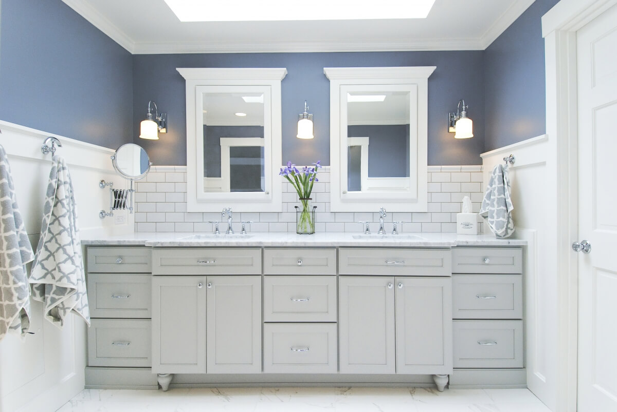 A cool gray painted master bathroom vanity with white subway tiles and blue painted walls.