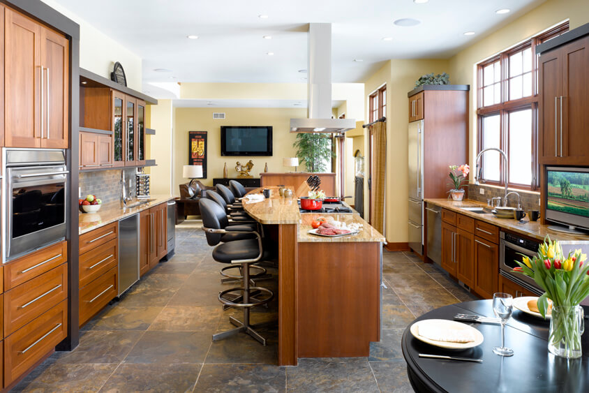 A warm stained contemporary ktichen with a long kitchen island with a cooktop and bar height seating.