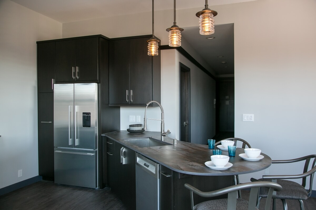 A dark black kitchen with dark stained cabinet from Dura Supreme Cabinetry in an industrial style city loft kitchen design.