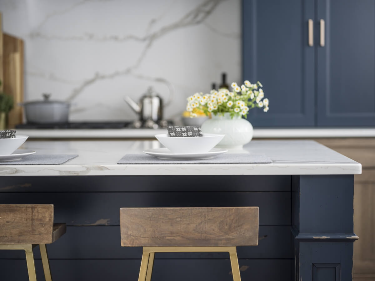 A close up of a navy blue kitchen island by Dura Supreme with gold bar stools and countertop height seating in the kitchen.