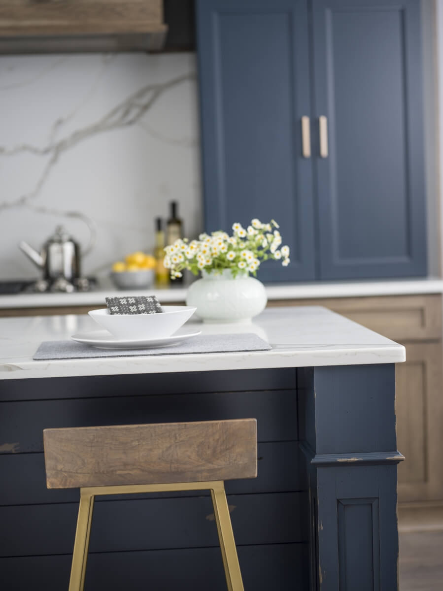 Navy blue and gray brown stained kitchen cabinets in a modern farmhouse styled kitchen remodel.