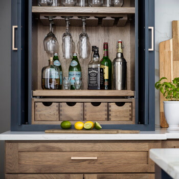 Dura Supreme Cabinetry Beverage Center Larder shown used for home bar storage.
