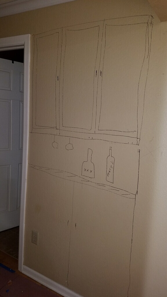 Before image of the wet bar remodel in the hallway. The designer drew on the wall to show where the cabinets and countertop will go.