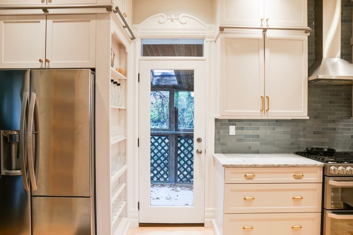 A view out the kitchen door showing the tall thin cabinet on the side of the fridge with open shelves for storage for cups, wine glasses, spices, canned goods and more.