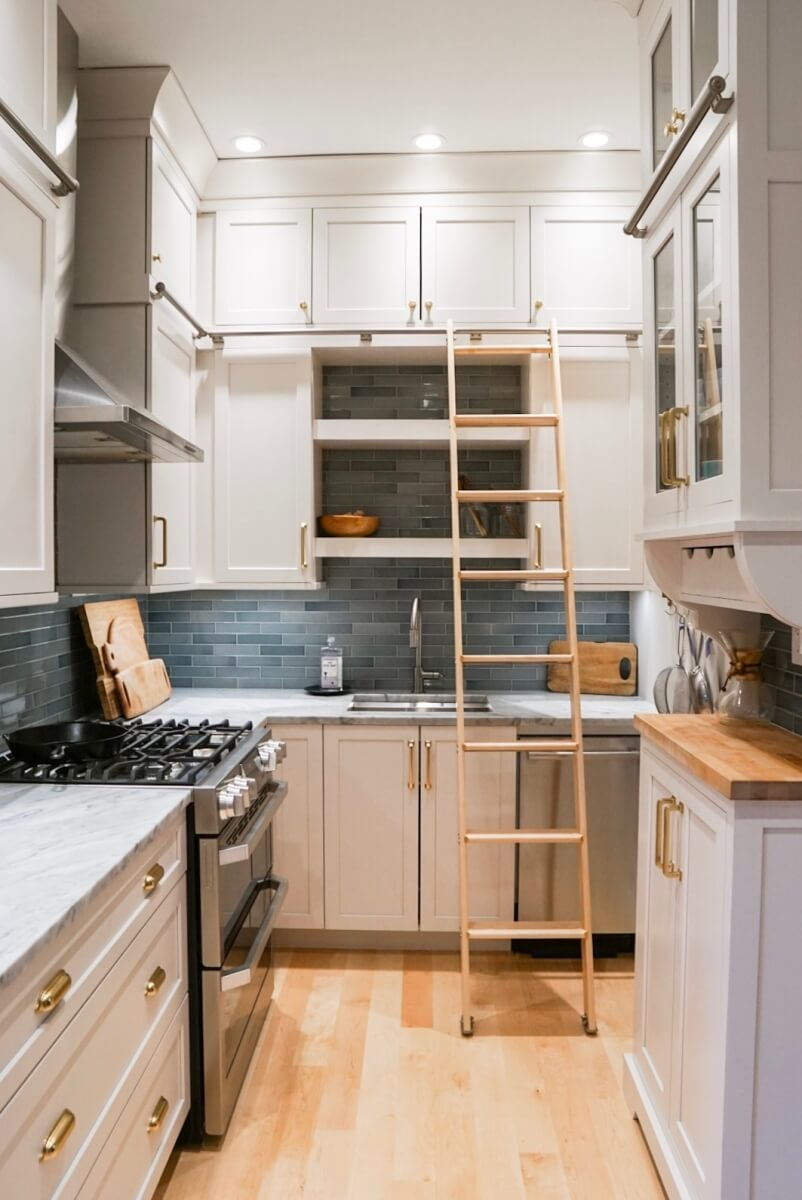 A small U-Shaped kitchen design in a historic home with white painted cabinetry and a library style ladder.