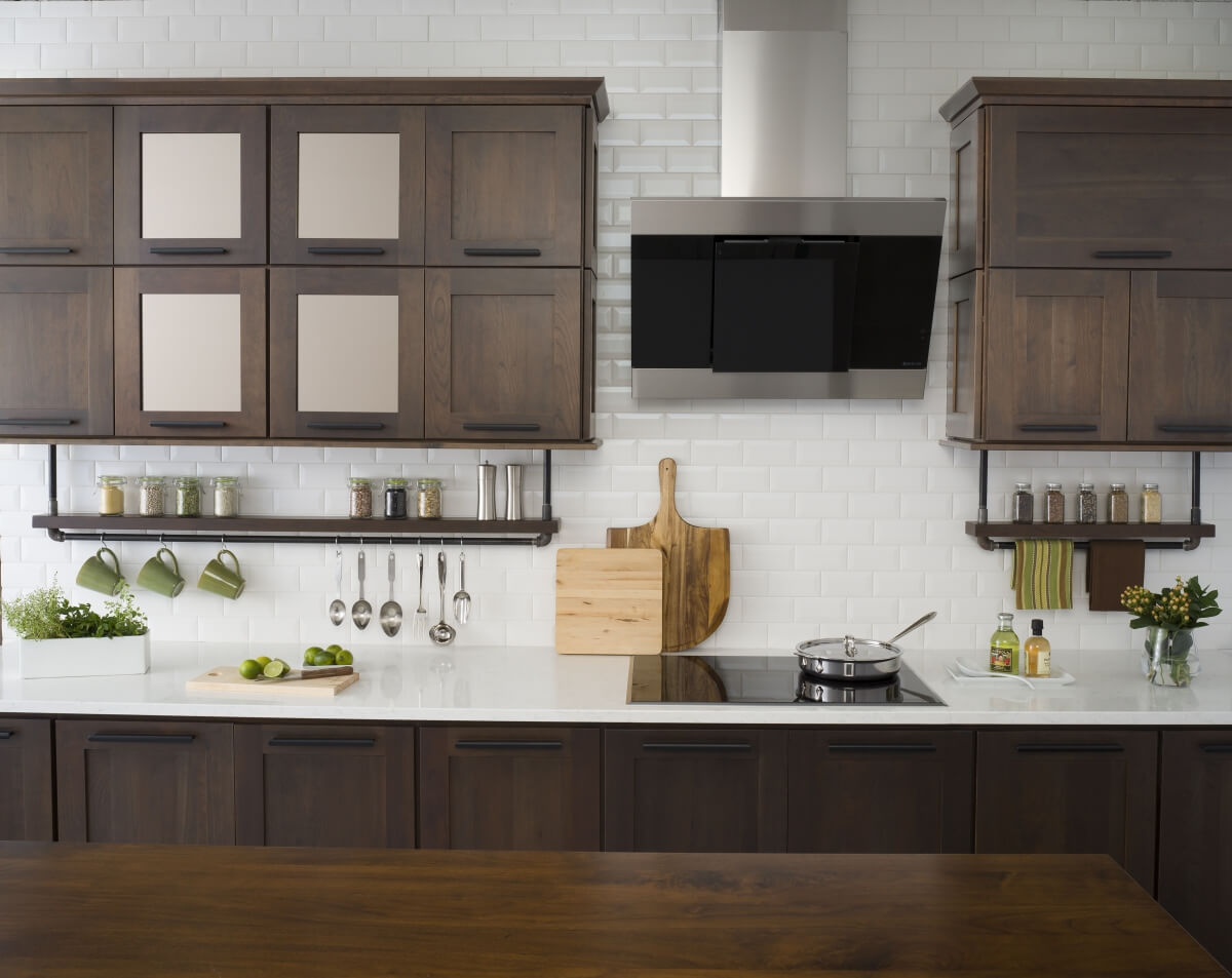 A modern industrial styled kitchen design with pipe floating shelves for spices, dark stained cabinets, and decorative bronze mirror cabinet doors.