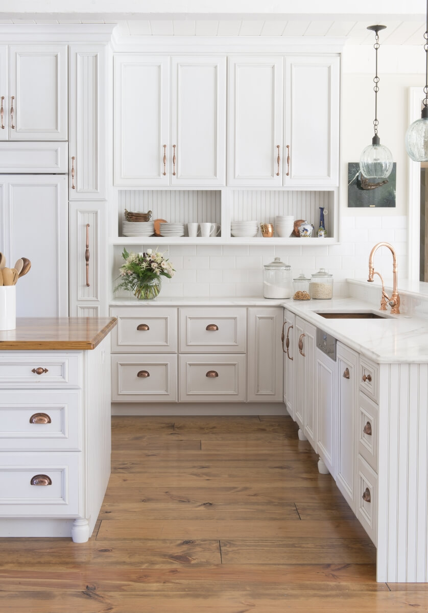 A bright white french farmhouse style kitchen with gold and brass hardware, white painted cabinets, white subway-tile backsplash and light stained wood floors.