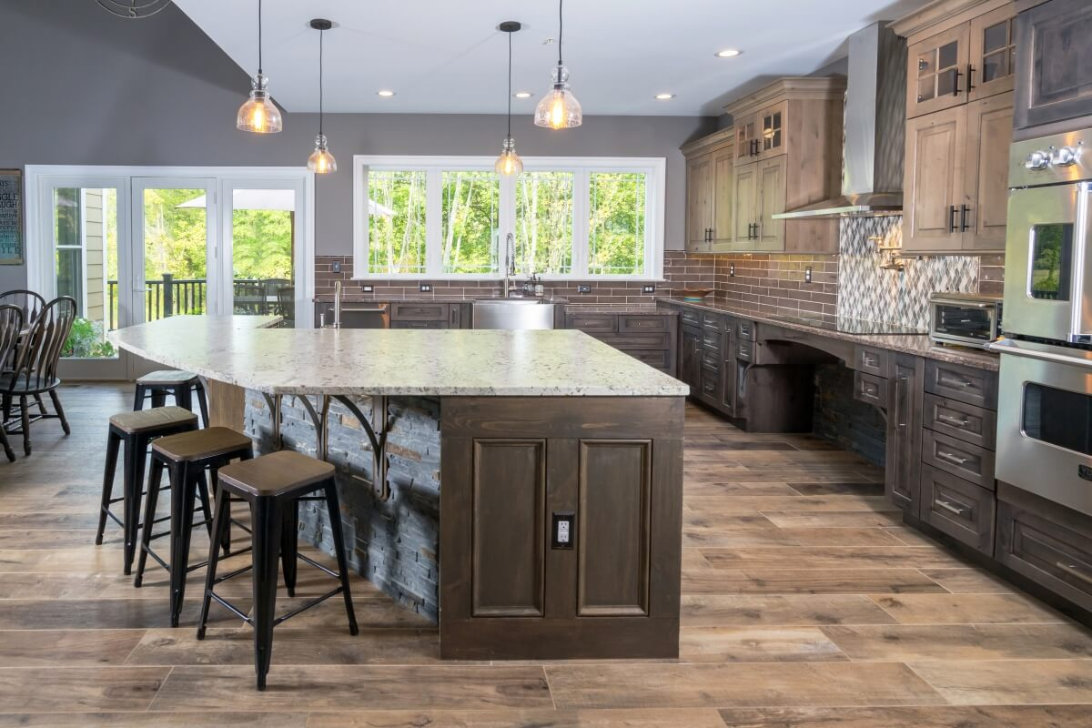 A rustic kitchen design with wheel chair accessible kitchen island, kitchen sink, cooktop, and additional accessible work zones.