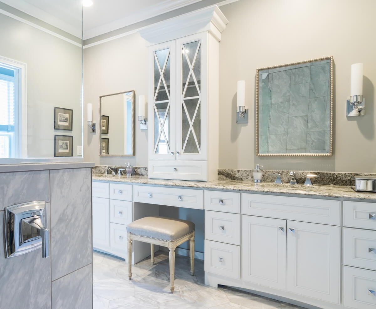 A double sink vanity with a tall tower in the center dividing the two spaces. The countertop sitting cabinets feature elegant mirrored cabinet doors and mullion designs.