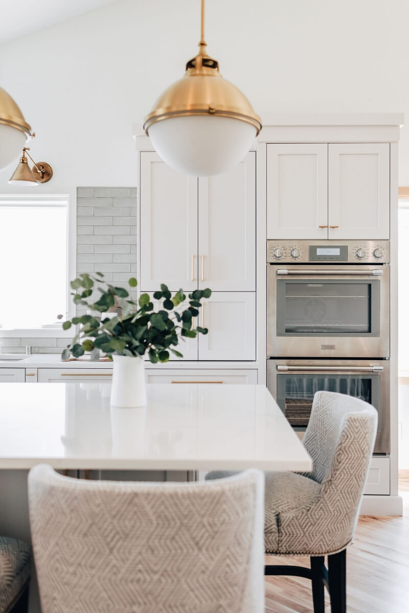 A beautiful all white kitchen with a kitchen island that features counter height seating that is easy for children to reach and sit.