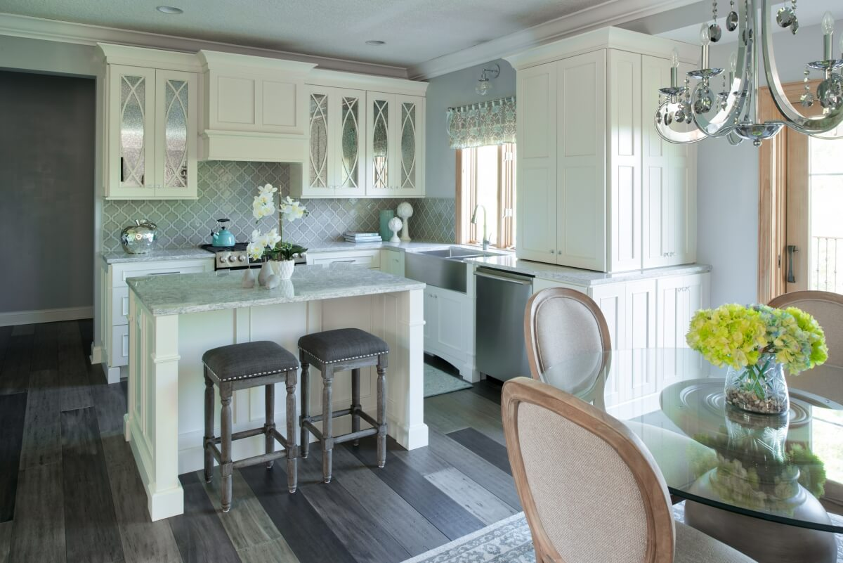 A bright white and reflective kitchen design with antique mirror cabinet doors.