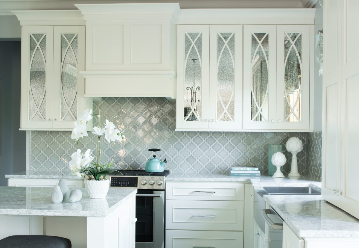 A white painted kitchen design with mullion cabinet doors and antique mirror glass insert.