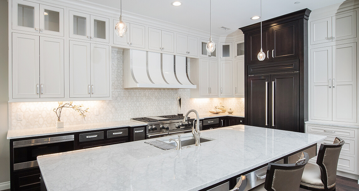A black and white kitchen design with a hidden appliance panel fridge. This design features high contrasting two-toned Dura Supreme kitchen cabinets.