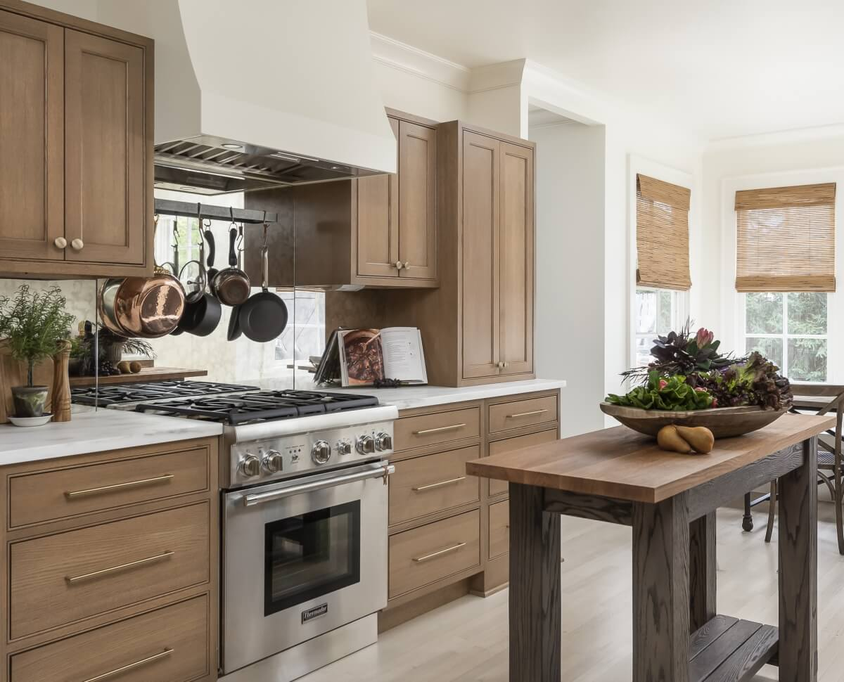 A light natural stained kitchen remodel with a white wood hood and trendy mirrored backspalsh is a bright and fresh design.