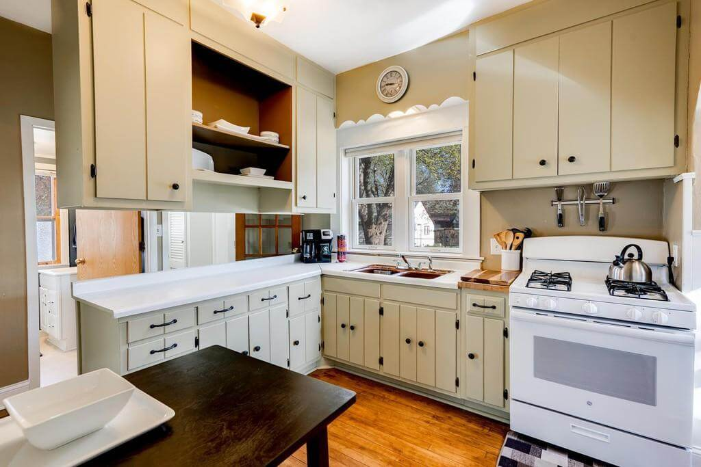 An old-fashioned kitchen design with a peninsula with ceiling hung upper cabinets.