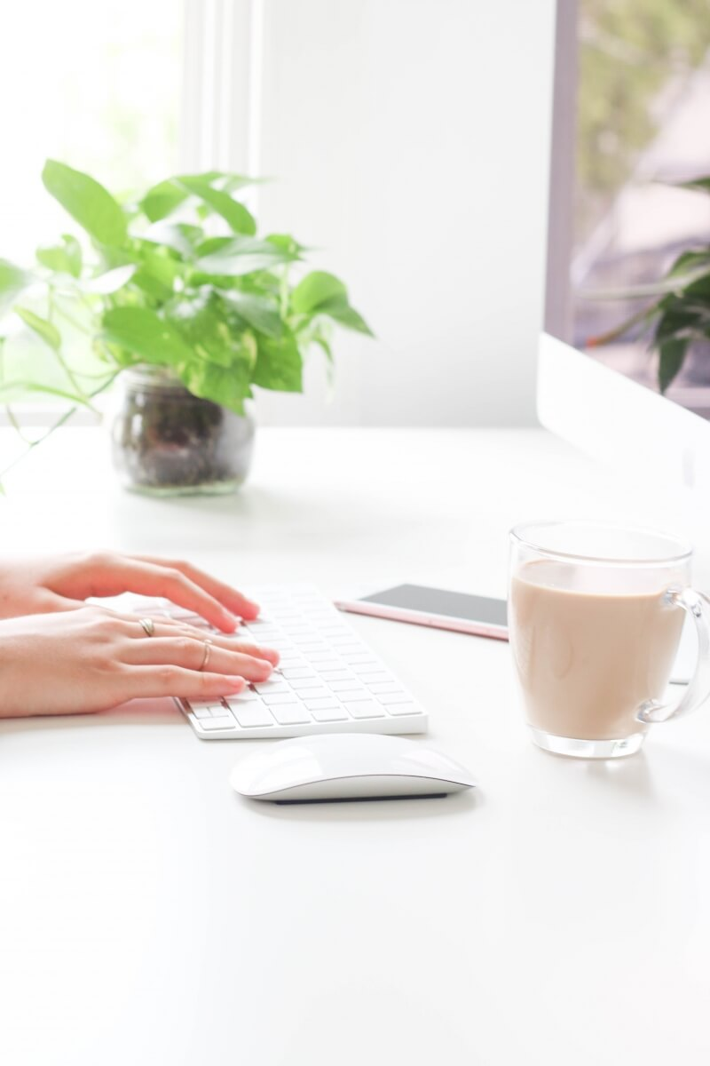 A pretty home office with bright white colors. A close up of someones hands working on a computer at their desk.
