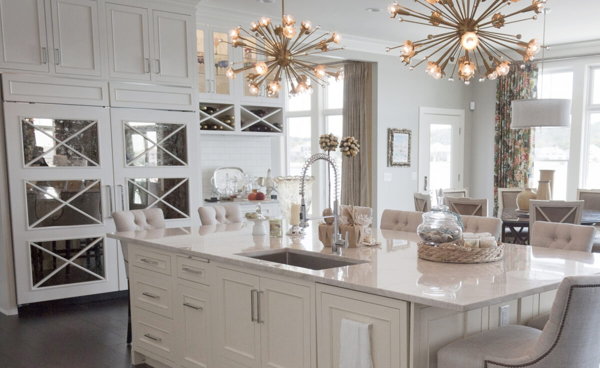 A stunning white and bright kitchen design with mirror cabinet door panels with an X pattern on the refrigerator.