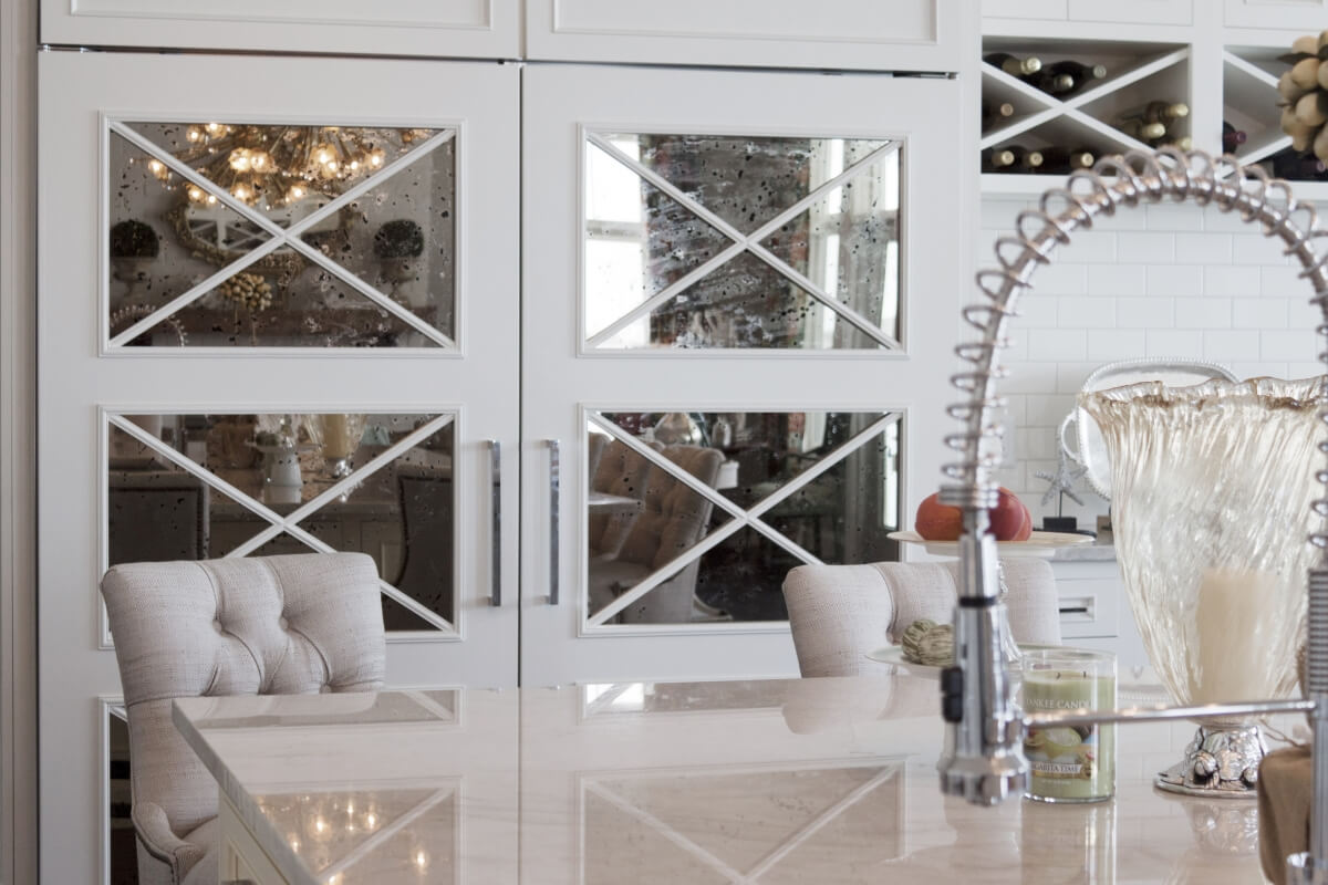 Mirrored cabinets with an X mullion cabinet door pattern. Mirrors on a large kitchen appliance, a kitchen fridge.