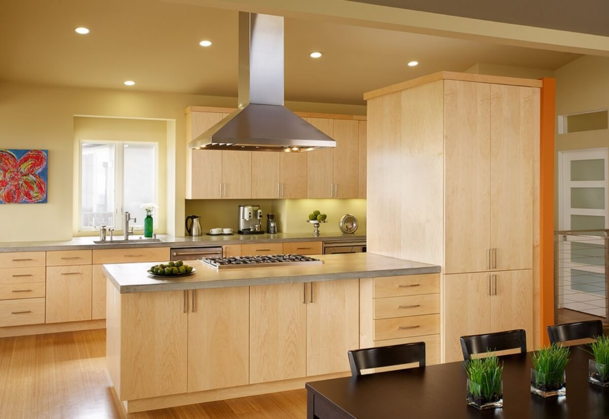 A modern styled kitchen with warm, light stained wood cabinets and a long kitchen peninsula with a cooktop and floating metal hood.