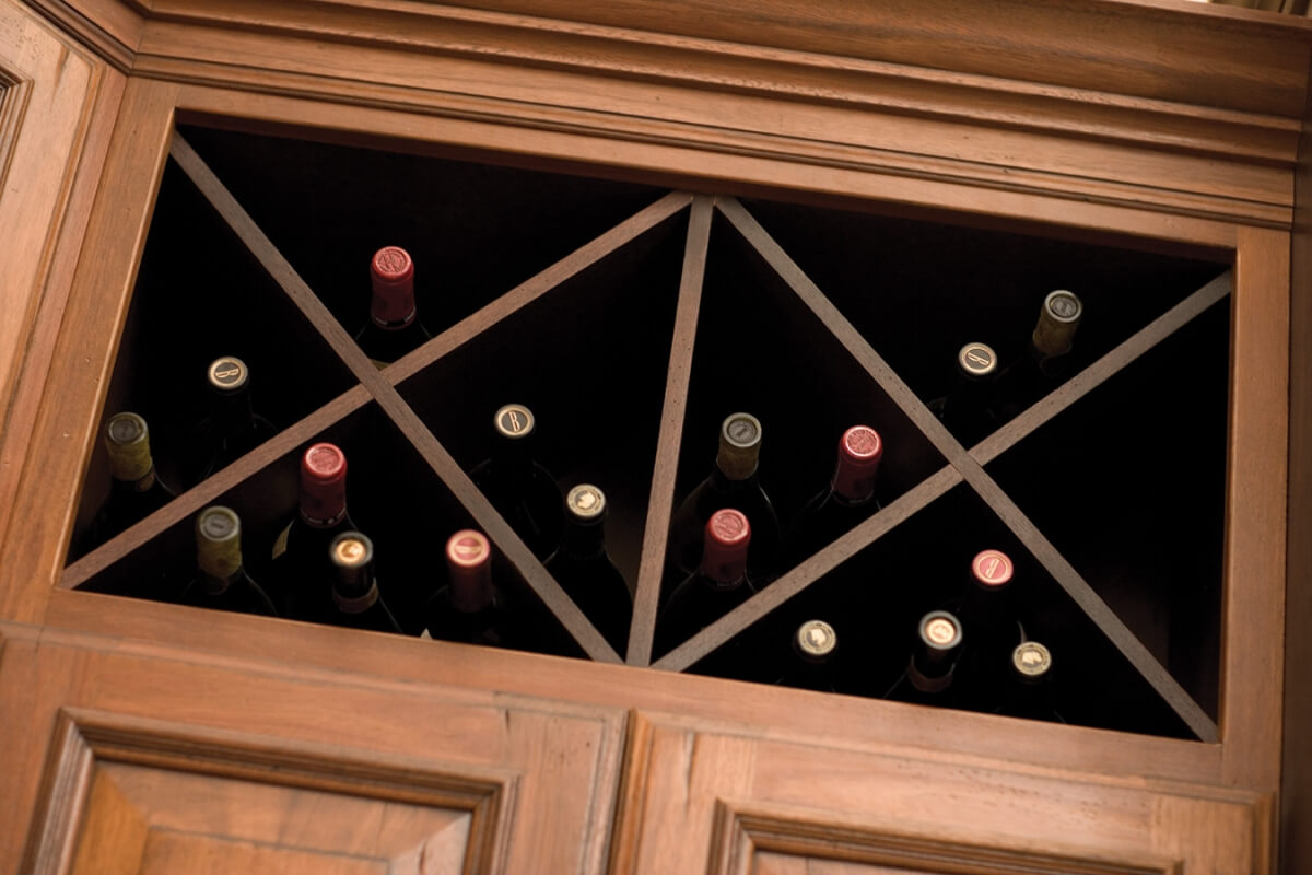 "An ""X"" wine rack in an open kitchen cabinet offers convenient and beautiful wine storage."