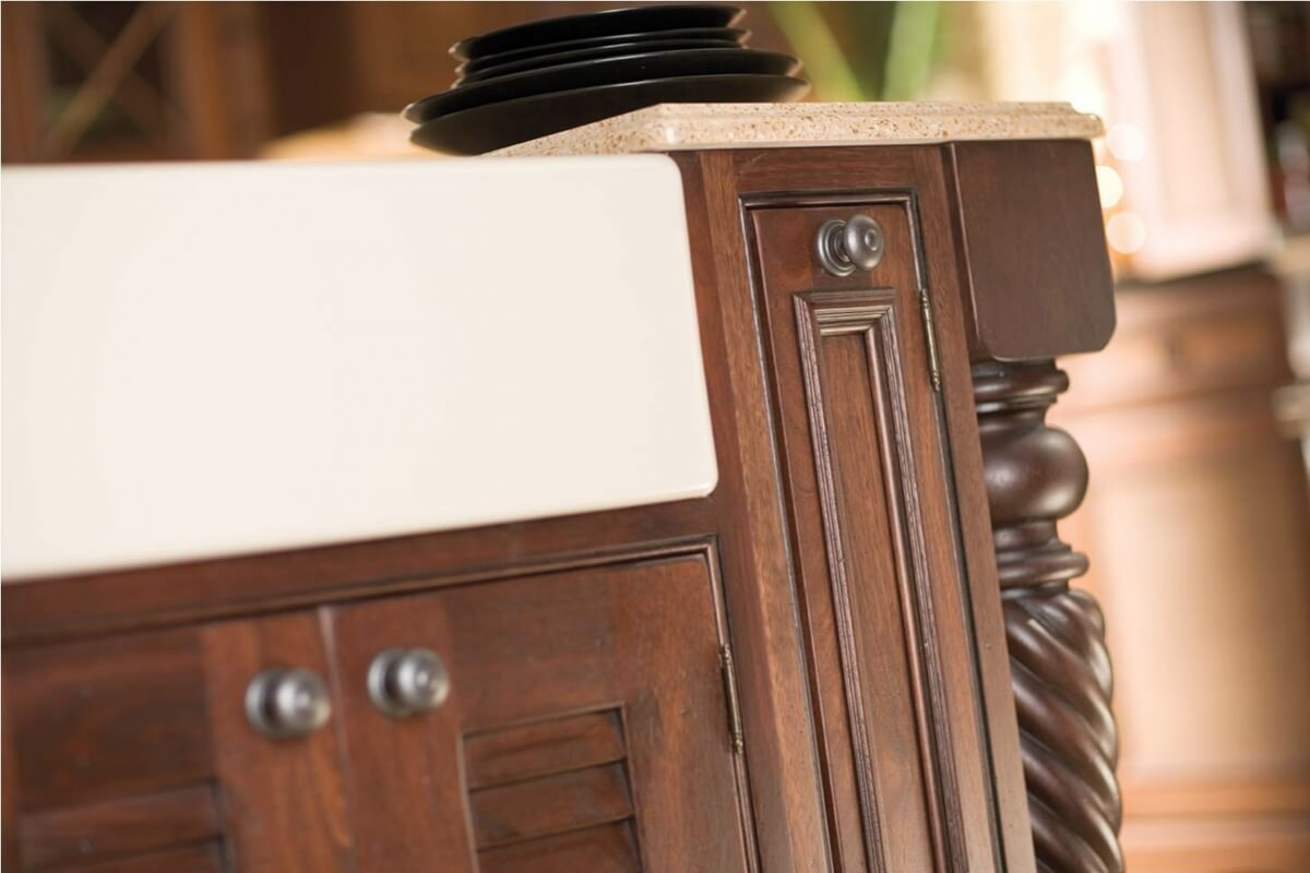 Inset cabinetry with decorative barrel hinges can help create the look of a historic piece of furniture.