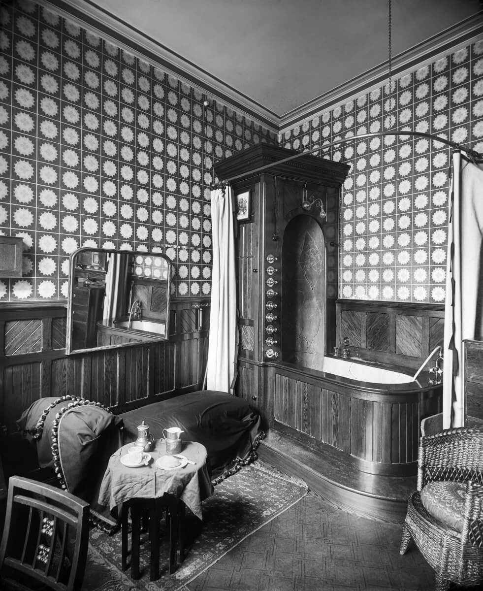 Victorian-Era bathroom furnished in wood, carpet and upholstered furniture