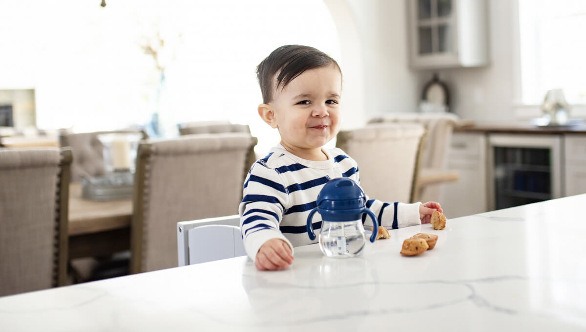 An adorable toddler sitting at a bar stool eating at a kitchen island with countertop height seating.
